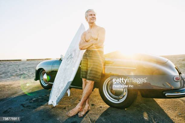Older Caucasian man on leaning on convertible car with surfboard