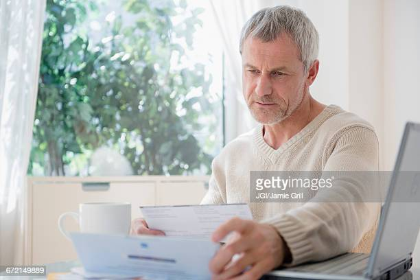 Older Caucasian man paying bills using laptop