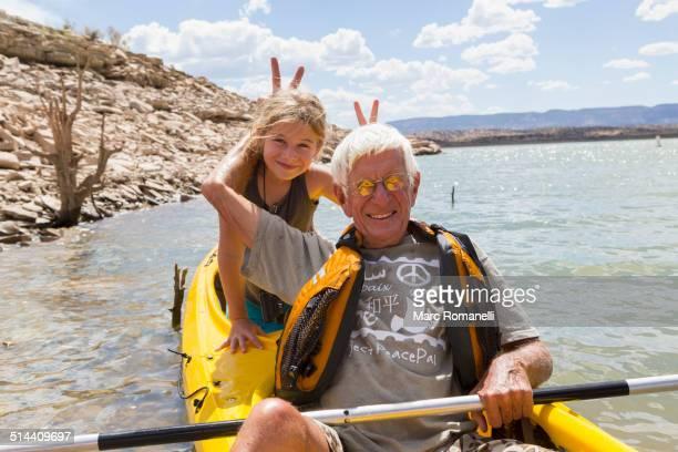 Older Caucasian man posing in kayak with granddaughter