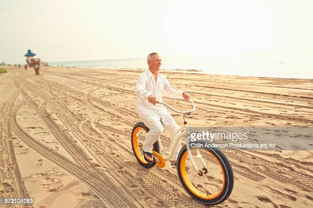 Older Caucasian man riding bicycle on beach