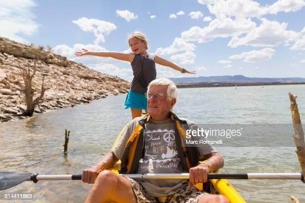 Older Caucasian man rowing kayak with granddaughter