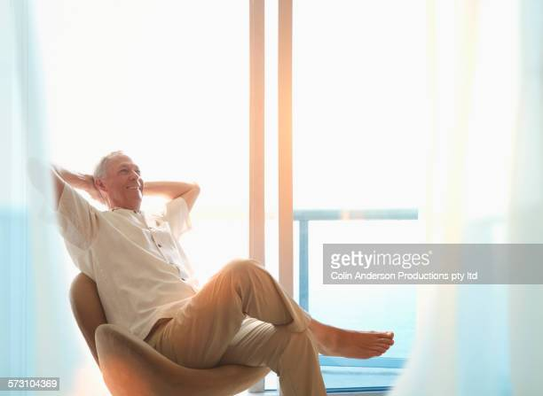 Older Caucasian man sitting at window
