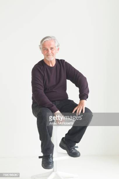 Older Caucasian man sitting on stool
