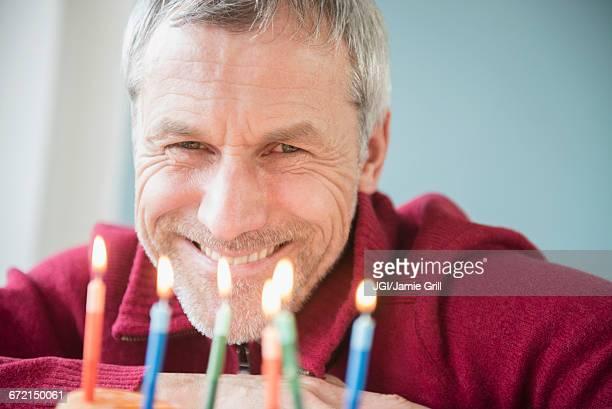 Older Caucasian man smiling at birthday cake