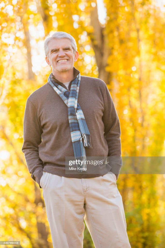 Older Caucasian man smiling near autumn trees : Foto stock