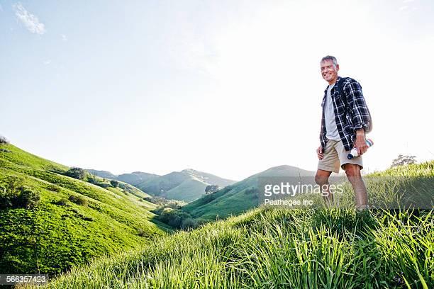 Older Caucasian man smiling on grassy hillside