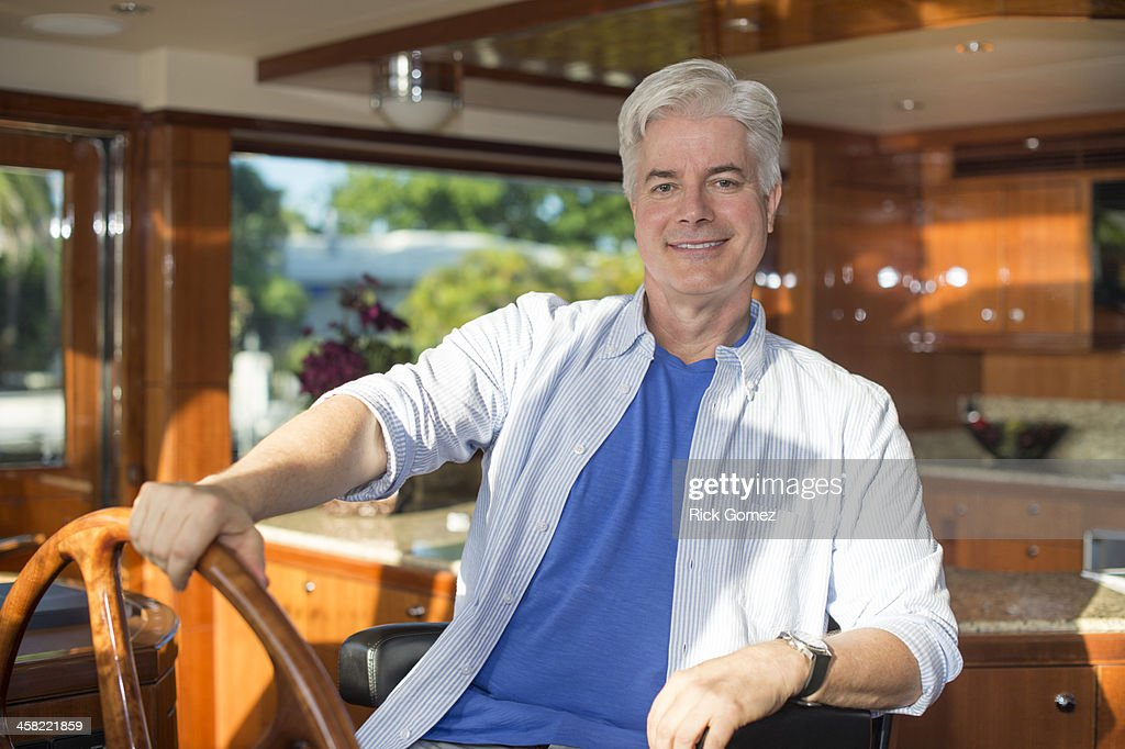 Older Caucasian man steering yacht : Stock Photo