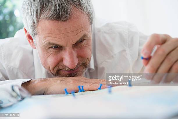 Older Caucasian man sticking pins in map