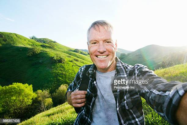 Older Caucasian man taking selfie on rural hilltop