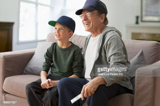 Older Caucasian man watching television with grandson