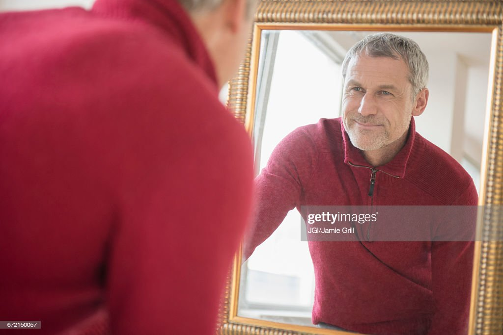 Older Caucasian man wearing sweater smiling in mirror : Stock Photo