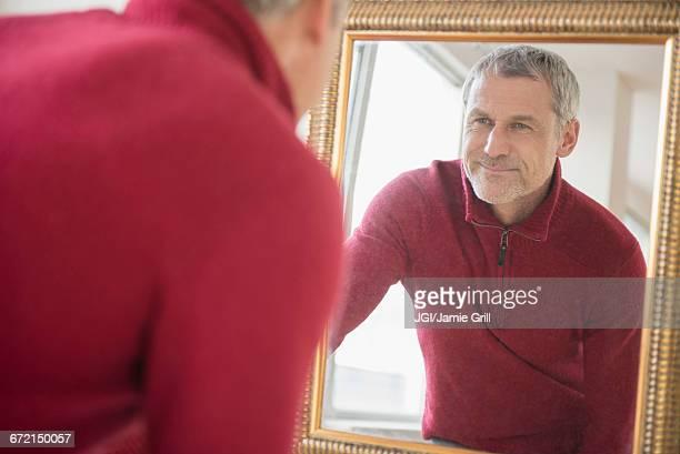 Older Caucasian man wearing sweater smiling in mirror