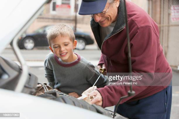 older caucasian man with grandson checking oil in car - oil change stock pictures, royalty-free photos & images