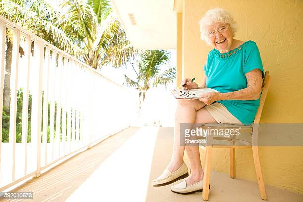 Older Caucasian solving crossword puzzle on balcony