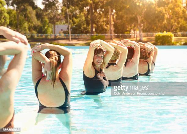 Older Caucasian synchronized swimmers performing in pool