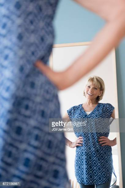 Older Caucasian woman admiring dress in mirror