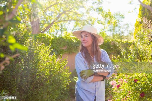 Older Caucasian woman admiring flowers in garden