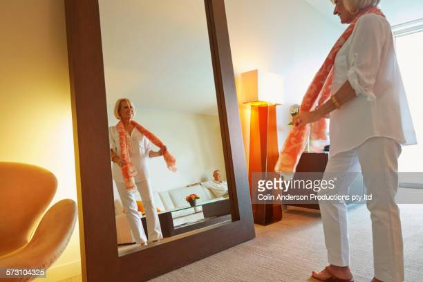 Older Caucasian woman admiring herself in mirror