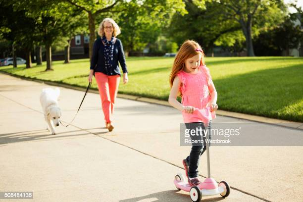 Older Caucasian woman and granddaughter walking dog on suburban street
