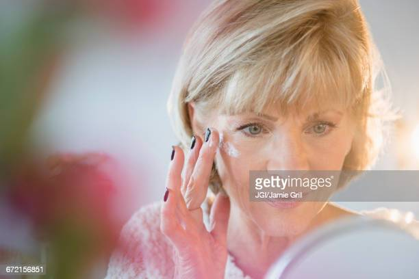 Older Caucasian woman applying moisturizer to face