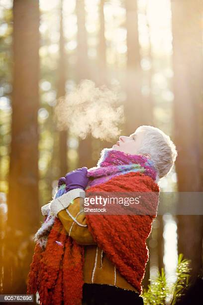 Older Caucasian woman breathing steam outdoors