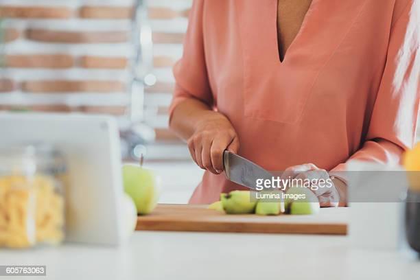 Older Caucasian woman cutting apples in kitchen