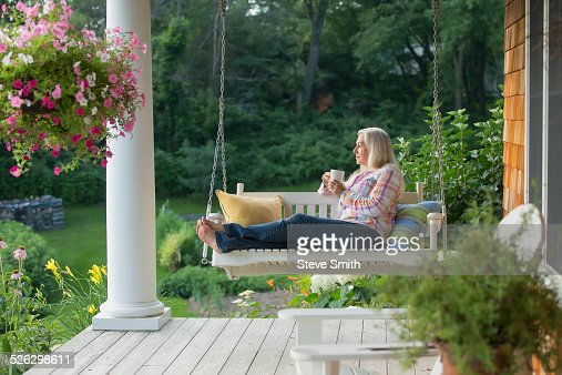 Older Caucasian Woman Drinking Cup Of Coffee On Porch