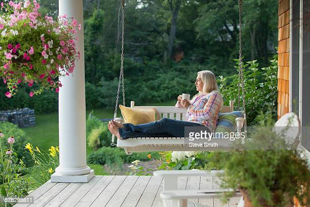 Older Caucasian woman drinking cup of coffee on porch swing
