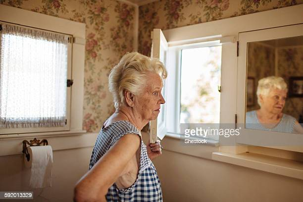 older caucasian woman examining herself in mirror - one senior woman only stock pictures, royalty-free photos & images