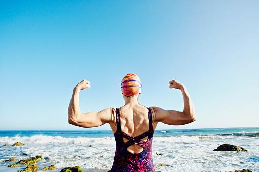 Older Caucasian woman flexing her muscles on beach - gettyimageskorea