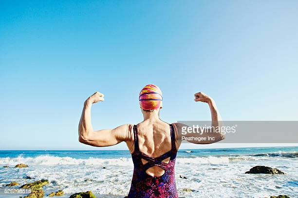 older caucasian woman flexing her muscles on beach - entschlossenheit stock-fotos und bilder