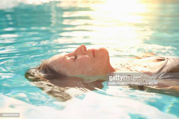 Older Caucasian woman floating in pool