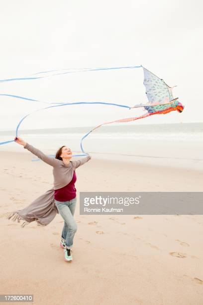 Older Caucasian woman flying kite on beach
