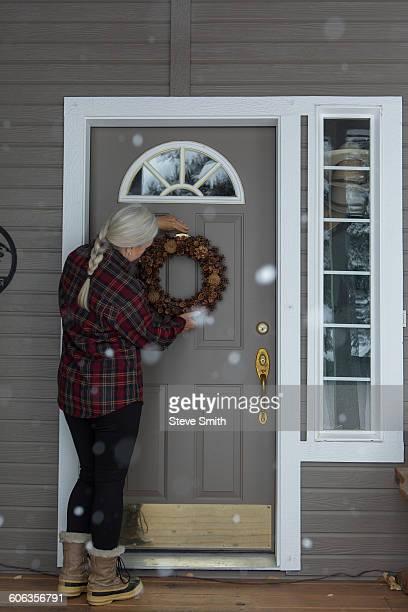 Older Caucasian woman hanging wreath on front door