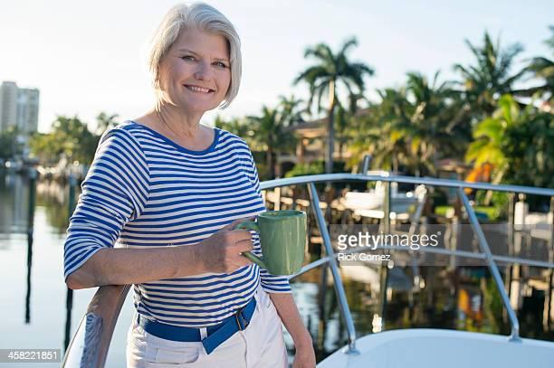 Older Caucasian woman having coffee on boat deck