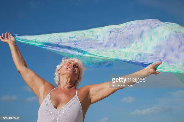 Older Caucasian woman holding fabric in wind under blue sky
