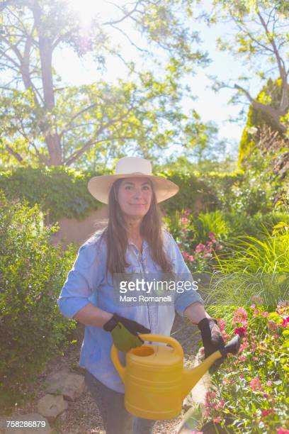 Older Caucasian woman holding watering can