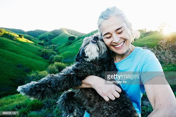 Older Caucasian woman hugging dog on rural hilltop