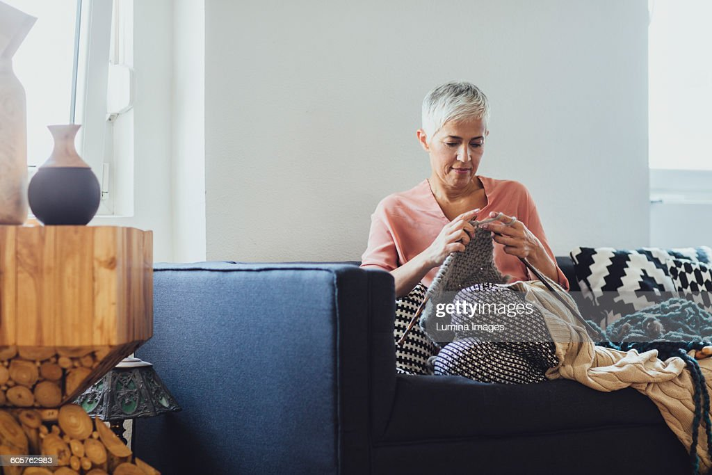 Older Caucasian woman knitting on sofa : Stock-Foto