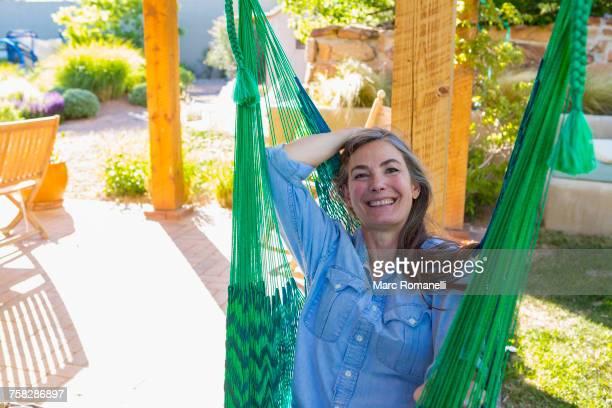 Older Caucasian woman laying in green hammock