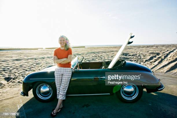 Older Caucasian woman leaning on convertible car with surfboard on beach
