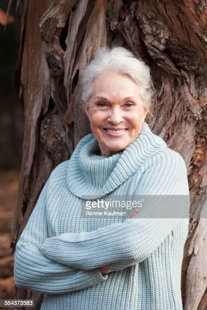 Older Caucasian woman leaning on tree