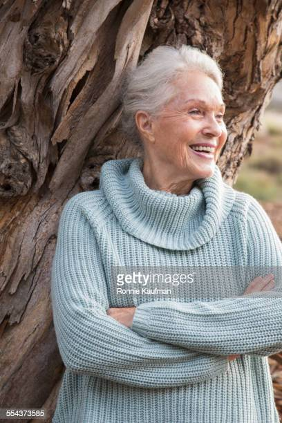 Older Caucasian woman leaning on tree