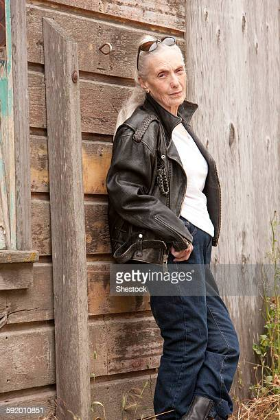 Older Caucasian woman leaning on wooden wall