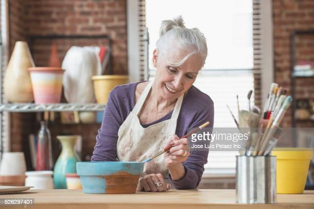 Older Caucasian woman painting pottery in studio