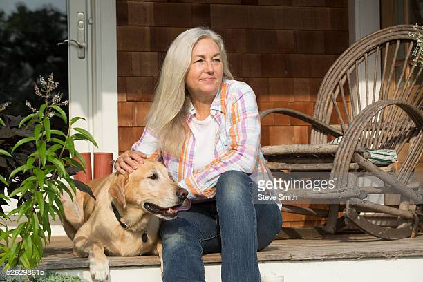 older caucasian woman petting dog on front porch - maisie smith stock pictures, royalty-free photos & images