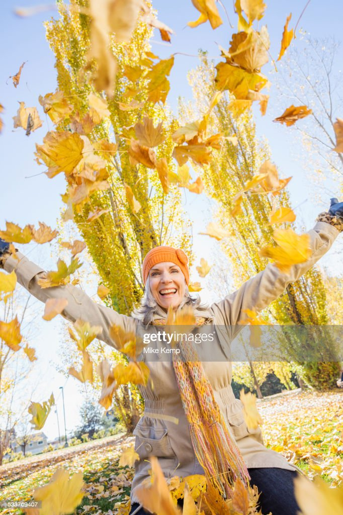 Older Caucasian woman playing in autumn leaves : Foto stock
