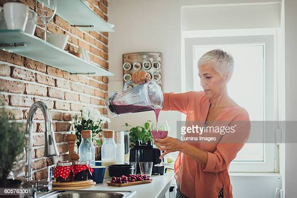 Older Caucasian woman pouring smoothie in kitchen