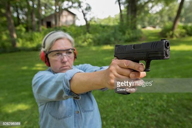 Older Caucasian woman practicing with gun at shooting range