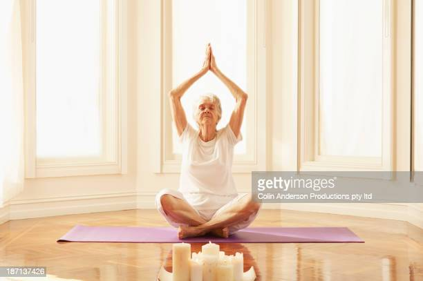 older caucasian woman practicing yoga - atmospheric mood stock pictures, royalty-free photos & images